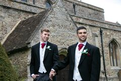 Gay wedding, grooms leave village church after being married with big smiles and holding hands. Gay weddings newly wed men, dressed in matching morning suits Stock Images