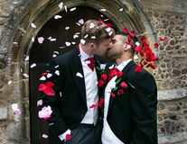 Gay wedding, grooms leave village church after being married to smiles and confetti. Gay weddings newly wed men, dressed in matching morning suits leave village Stock Photo