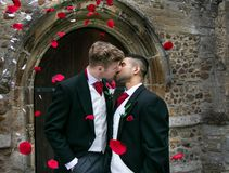 Gay wedding, grooms leave village church after being married to smiles and confetti. Gay weddings newly wed men, dressed in matching morning suits leave village royalty free stock image