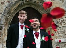 Gay wedding, grooms leave village church after being married to smiles and confetti. Gay weddings newly wed men, dressed in matching morning suits leave village Royalty Free Stock Photo