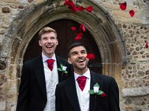 Gay wedding, grooms leave village church after being married to smiles and confetti. Gay weddings newly wed men, dressed in matching morning suits leave village Stock Images