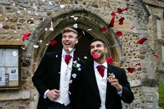 Gay wedding, grooms leave village church after being married to smiles and confetti. Gay weddings newly wed men, dressed in matching morning suits leave village royalty free stock photos