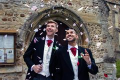 Gay wedding, grooms leave village church after being married to smiles and confetti. Gay weddings newly wed men, dressed in matching morning suits leave village royalty free stock images