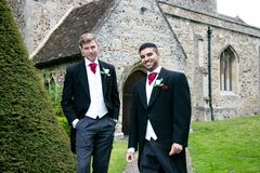 Gay wedding, grooms leave village church after being married with big smiles and holding hands. Gay weddings newly wed men, dressed in matching morning suits Royalty Free Stock Photos