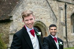 Gay wedding, grooms leave village church after being married with big smiles and holding hands. Gay weddings newly wed men, dressed in matching morning suits Stock Image
