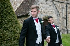 Gay wedding, grooms leave village church after being married with big smiles and holding hands. Gay weddings newly wed men, dressed in matching morning suits Stock Photography