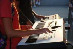 Gay y muchacha que juegan en un sintetizador en puesta del sol del th Fotografía de archivo libre de regalías