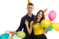 Gay young guy with a girl with cones on their heads carrying balloons and laughing Stock Photography