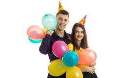 Gay young guy and girl are holding a lot of balloons and smiling Royalty Free Stock Photos