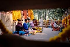 GAYA, INDIA - DECEMBER 3, 2016: De boeddhistische mannen en de vrouwen bidden en mediteren in Bodh Gaya Stupa Stock Foto's