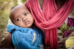 GAYA, INDIA - 3 DICEMBRE 2016: Una mamma indiana porta il suo giovane bambino elemosinare soldi immagine stock