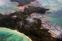 Gaya island poverty and paradise. KOTA KINABALU/MALAYSIA - NOVEMBER 2015: Aerial view of Gaya Island, a tropical paradise with sandy beaches from one side and an Stock Photo