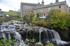 Gayle Beck Waterfalls in Hawes. Yorkshire Dales National Park North of England. Shot with fast shutter speed, Traditional village cottages in background stock images