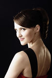 Gaze over shoulder. Young woman's gaze over shoulder photo over dark Royalty Free Stock Photo