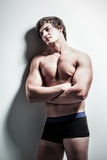 The gaze. Portrait of a handsome caucasian male model leaning against the studio wall with his arms crossed dressed in black and blue underwear Stock Images