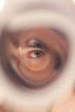 Gaze through tube. Eye looking trough tube selective focus Stock Photos