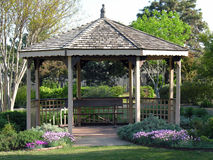 Gazebo. A small gazebo surrounded by flowerbeds and trees in the park royalty free stock image