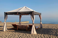 Gazebo beds on sand summer beach, Greece Stock Image