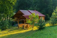 Gazebo with a bench and a spruce on the background of a wooden house. For your design royalty free stock photo