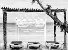 Gazebo blanco de madera por la playa con las sillas largas debajo de él-HDR-BandW imagen de archivo libre de regalías