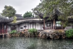 The gazebo in the chinese garden. Small pond, rocks around and the gazebo are traditional architectonical elements of chinese gardens Royalty Free Stock Photography