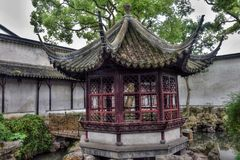 The gazebo in the chinese garden. Small pond, rocks around and the gazebo are traditional architectonical elements of chinese gardens Stock Photo