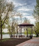 Gazebo Close to the River. Gazebo with wooden benches, in the Naltalka park of Kiev, Ukraine, near the Dnieper river, during a cloudy spring morning Stock Photos