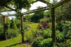 Gazebo de la pérgola en un jardín hermoso foto de archivo