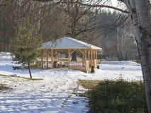 Gazebo de madera grande de la alcoba con el banco en abedul de la nieve del invernadero Imagen de archivo libre de regalías