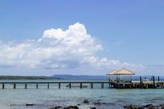 Gazebo del mar y calzada de madera que llevan al mar de la playa con la nube blanca grande en fondo y la piedra en el mar imágenes de archivo libres de regalías