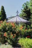 Gazebo del parque detrás de un arbusto color de rosa fotos de archivo libres de regalías