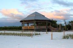 Gazebo di legno alla spiaggia nel tramonto Immagine Stock