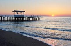 gazebo en el embarcadero de madera en el mar con el sol en la puesta del sol Foto de archivo