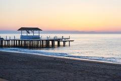 gazebo en el embarcadero de madera en el mar con el sol en la puesta del sol Foto de archivo libre de regalías