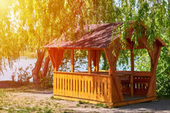 Gazebo for family entertainment and is made of wood, stands on the shore of the lake Royalty Free Stock Photography