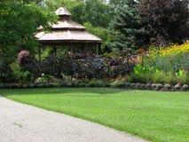 Gazebo, flores e gramado de madeira Foto de Stock Royalty Free