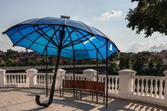 A gazebo in the form of a large blue umbrella against a white fence. stock images