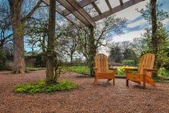 Gazebo-Garten mit Holzstühlen Lizenzfreie Stockfotos