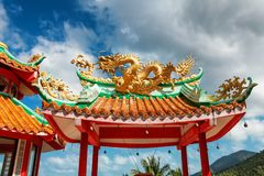Gazebo with a golden dragon on the roof of Chinese Sangthom Temple of the Goddess of Mercy Shrine in Chaloklum, Ko Pha Ngan, Thail. And Showing the ornate stock images