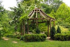 Gazebo in green garden. Wooden gazebo on green grassy lawn in sunny garden royalty free stock photography