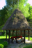 Gazebo with a hay roof in the garden Stock Photos