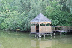 Gazebo by the lake. Wooden arbor on the lake in the city park Stock Image
