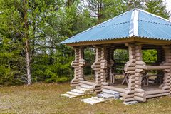 Gazebo made of logs on the edge of the forest to relax and picnic in the fresh air Stock Images