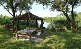 Gazebo med dekorativa lantliga träbänkar som servicepoler på bankerna av floden på gryning arkivbilder