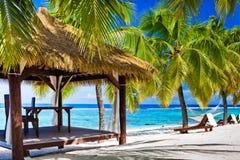Gazebo mit Stühlen auf einsamem Strand mit Palmen Lizenzfreies Stockfoto