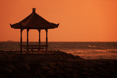 Gazebo on the ocean shore at sunset. Indonesia, Bali Royalty Free Stock Images