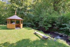 Gazebo och bänk för avkoppling på en grön matta av gräs på banken av en skogflod Royaltyfria Bilder