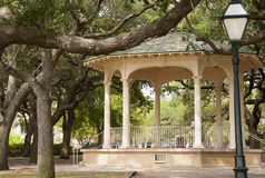 Gazebo in the Park. A large gazebo and street light in a public park surrounded by Live Oak trees Royalty Free Stock Photo