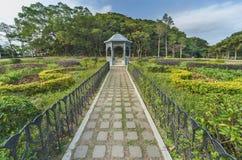 Gazebo in park. Idyllic view of flower garden royalty free stock image