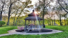 Gazebo in a park with trees around. stock image